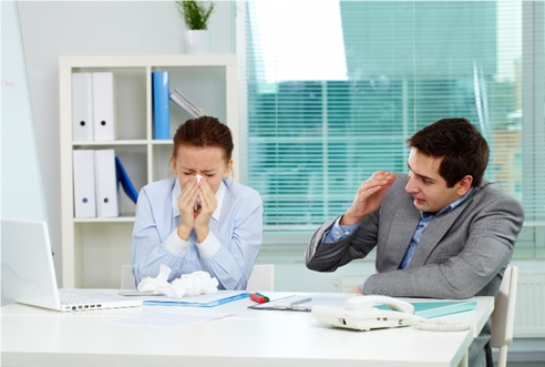 woman sneezing into a tissue next to a male co-worker hiding his face