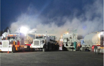 Clouds of dust are visible as sand trucks are unloaded at a hydraulic fracturing site.