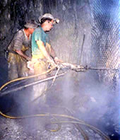 miners drilling rock, dust cloud