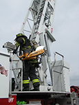 A firefighter is climbing an aerial ladder while in gear.