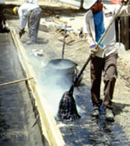 applying hot asphalt to a roof