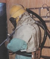 a worker wearing protective equipment while abrasive blasting