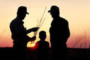 Two men and a child silhouetted in the sunset on a family farm