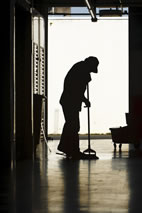 Silhouette of a janitor mopping a floor in a factory