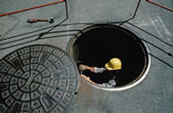 Worker entering manhole