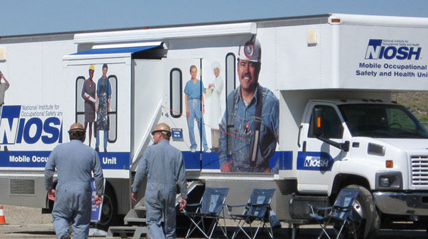 Two miners approach a NIOSH mobile health unit