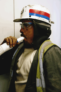 A miner blowing into a tube for lung function testing