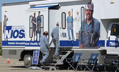 Two men in gear standing in front of NIOSH mobile screening unit