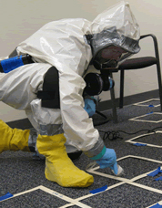 man in hazmat suit scraping anthrax off of floor