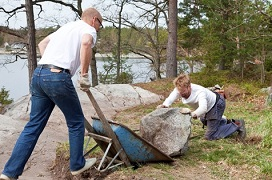 one man dumping a huge boulder and another man retrieving it - awkward postures