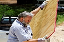 men caring a large panel of plywood