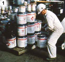 Worker lifting paint cans stacked on pallet