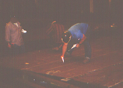 Worker bending over to mark the plate at floor level using chalk or paint markers