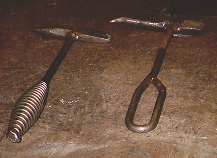 A coiled-handled hammer on left and a loop-handle hammer on right
