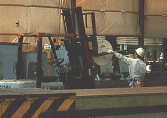 Worker using a a forklift to move cable spool