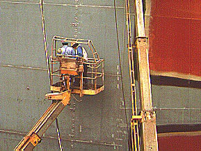 Workers using powered manlift along the side of a ship.