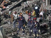 Rescue workers at building collapse site.