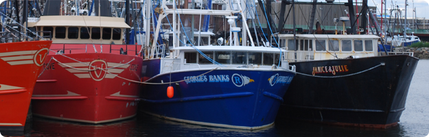 A close up photo of three New Bedford commercial fishing boats tied up at the dock.
