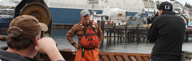 An image of a photo shoot for the Live to be Salty project being conducted on the deck of a crab vessel in Seattle, WA