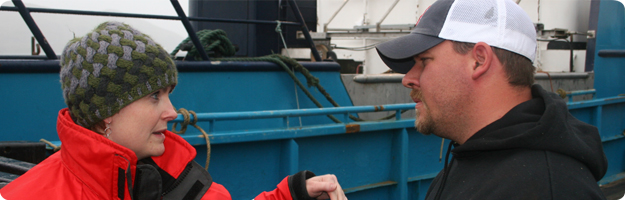 A NIOSH researcher discusses man overboard safety with the skipper of a crab vessel during a survey in Dutch Harbor, AK with the skippers vessel in the background.