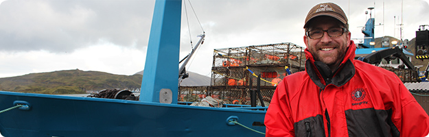 An image of a NIOSH researcher posing for photo in front of a Bering Sea crab vessel in Dutch Harbor, AK