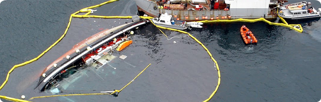 Aerial photo of a partially submerged commercial vessel with oil containment booms surrounding the vessel and a larger vessel beginning salvage operations.