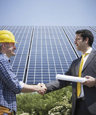 Image of workers shaking hands in front of a building certified as green