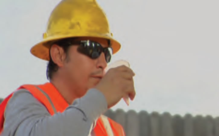 A Construction worker takes a drink of water.