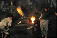 Workers casting hot metal