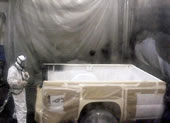 worker spraying truck bed