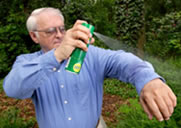 image of spraying deet on clothing