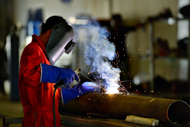 Image of worker wearing personal protective clothing welding a large pipe.