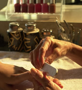 Hand shot of a manicurist filing a customer's fingernails