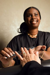 A manicurist smiles as she files her customer's fingernails