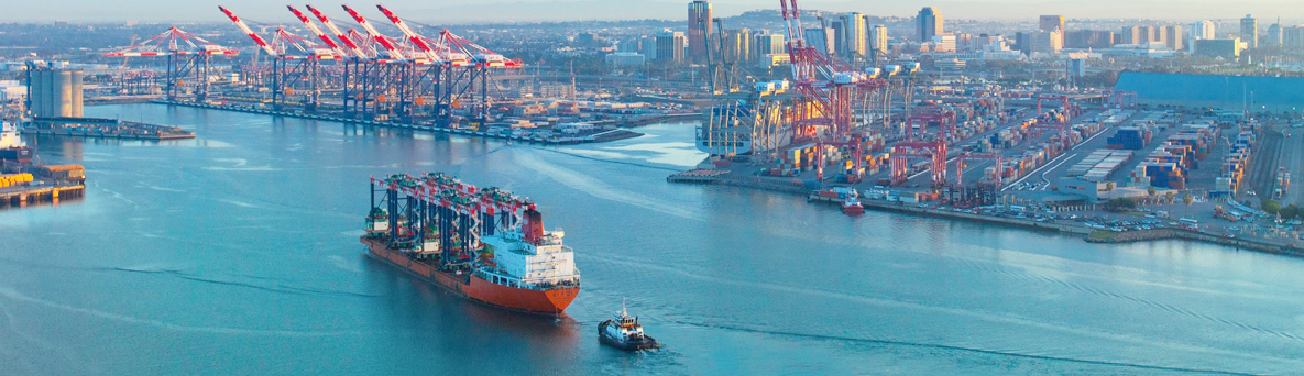 A tugboat assists a cargo container crane ship entering the Port of Long Beach. Image courtesy of Port of Long Beach.