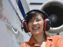 Woman wearing hearing protection while standing next to plane.
