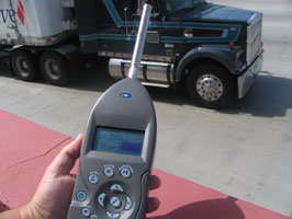 Image of sound meter and tractor trailer truck.
