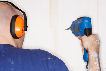 Image showing a construction worker using a drill and wearing hearing protection