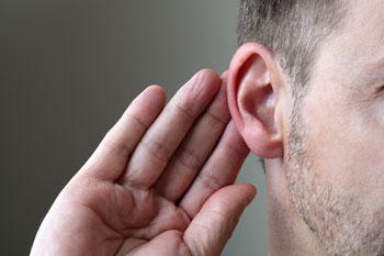 Image showing a person with his hand behind his ear trying to hear