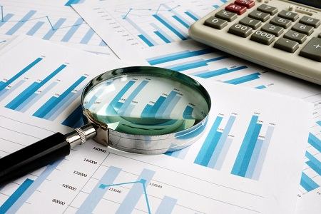 Business papers with financial report and magnifying glass