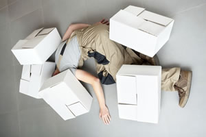 Employee lies on floor covered by boxes, as if the worker had fallen, and the boxes landed on him or her.