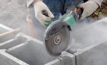 Worker cutting through bricks.