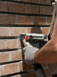 Bricklayer using a tuck-pointing grinder equipped with an on-tool dust control to remove mortar from a brick wall
