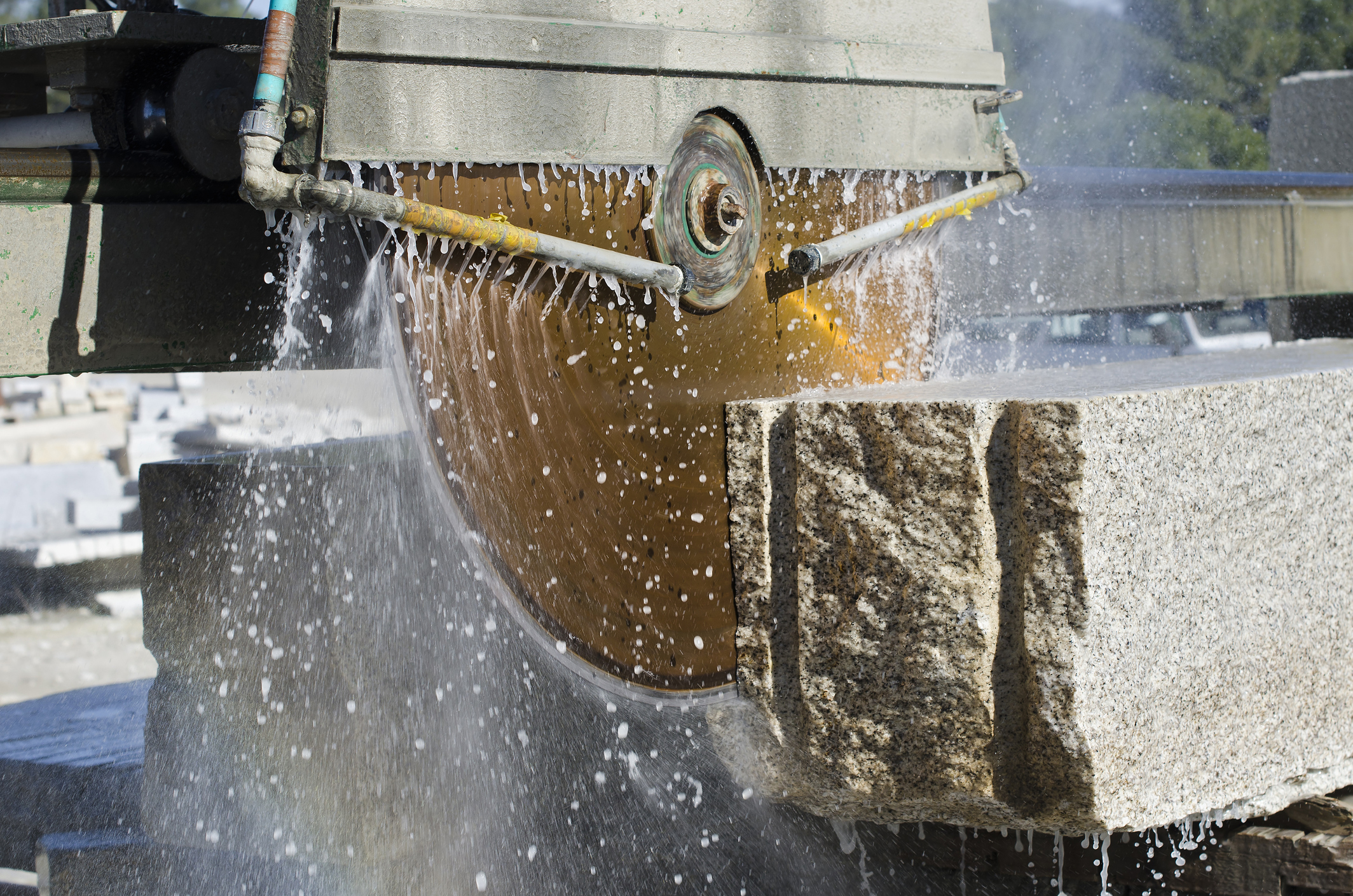A wet cutting blade sawing through concrete slab.
