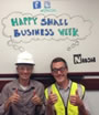 Two people giving thumbs-up infront of a whiteboard which says Happy Small Business Week