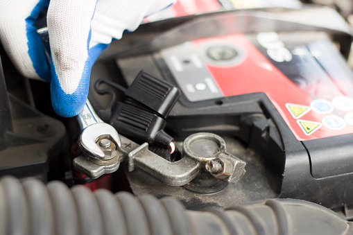 Image of a battery and a mechanic's hand wearing protective gloves turning a bolt with a wrench.