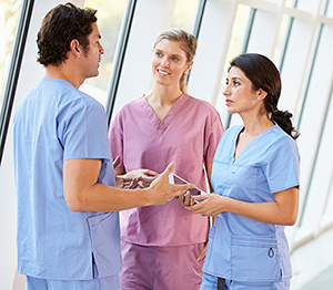 three nurses talking in hallway