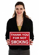 woman holding a sign says thank you for not smoking