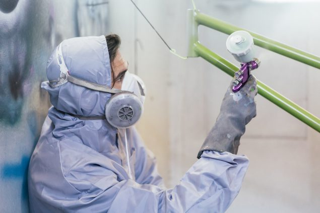 Image of worker wearing personal protective clothing spray painting a bike.