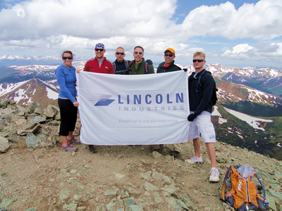Lincoln industries employees atop a mountain